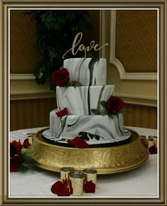 Black, gray and white marbled fondant wedding cake with gold accents.