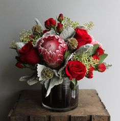 Holiday centerpiece with proteas, roses, eucalyptus, lamb's ear, and scabiosa pods