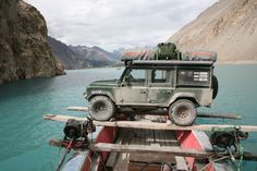 Land Rover Defender on Boat. Notice two tents on top mounted in opposing fashion. Also note the boat engines are strapped to both sides of the large boat, giving it more maneuverability