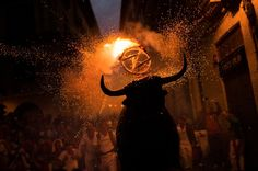 """TORO DE FUEGO  A flaming fake bull """"Toro de fuego"""" runs after revelers during the 2014 San Fermin fiestas in Pamplona, Spain, Wednesday, July 9, 2014. Revelers from around the world arrive to Pamplona every year to take part in some of the eight days of the running of the bulls. Credit: AP Photo/Andres Kudacki Read that an American who co-authored a book about the festival, was killed yesterday."""