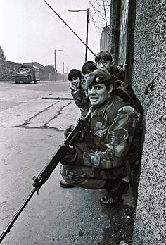 Innocence amid violence: Northern Irish children take cover behind a British Army trooper during The Troubles in Belfast, 1986. Being next to the soldier could easily mean injury or death if the main target was to come under fire from IRA gunmen. Note the soldier's  L1A1 Self-Loading Rifle (known as the 'inch pattern FAL' in the US) the standard issue for the British Army in those days. Courtesy of http://wwii.picturesofwar.net/