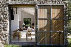 High-Style Sustainability in Spain : Remodelista - A hinged barn door made of oak and steel. The portal perfectly frames the dining area.