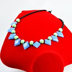 Give the retro lover in your life blue diamonds. This 16-inch midcentury modern necklace features opaque blue, green and black glass beads. Made to resemble the brightly colored jewelry of the postwar era, this bold look goes well with the vivid color blocks and patterns of the Mad Men era. The strand is closed in the back by a black toggle clasp.  The Smallest Planet Guarantee  All Smallest Planet jewelry is handmade by me, Sara Kelly, in my home studio in San Diego, California. As a…