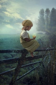 I remember doing this.  Not sure what she's holding but I remember the pasture, the fence, the trees :)