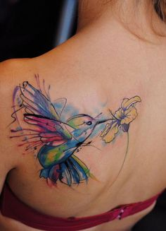 This tattoo has been drawn in a brilliant watercolor style. It has a combination of various colors such as blue, yellow, pink, black and white too. It shows a flying hummingbird sipping nectar from a yellow flower. Large in size, the art occupies the left shoulder-blade. #tattoofriday #tattoos #tattooart #tattoodesign #tattooidea