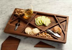 """The Puzzle"" wine tray, named after Newton's icon blend, combines 10 removable puzzle pieces that can be popped out to serve as coasters or smaller, individual serving trays for fruits, nuts, cheese and other wine-paired snacks. Each of the 112 pieces is handcrafted from responsibly sourced walnut wood, reflecting the eco-conscious ethos of the winery."
