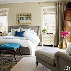 Painted in Farrow & Ball's Old White, the master suite is anchored by a Williams-Sonoma Home bed upholstered in a Ralph Lauren Home tweed. Christopher Spitzmiller lamps top bedside tables from Mecox, the stool at the foot of the bed is a Todd Alexander Romano design, and the armoire in the corner is antique Biedermeier Photo by WIlliam Waldron.