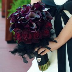 Burgundy And Purple Bouquet    Burgundy roses, purple calla lilies, and black feathers comprise a gorgeous, gothic-inspired bouquet