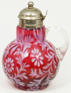 NORTHWOOD DAISY AND FERN CRANBERRY SYRUP w LID Northwood, West Virginia, 1901-1925. A Northwood cranberry opalescent glass syrup pitcher, Daisy and Fern pattern, metal flip lid, and clear, ribbed applied handle.