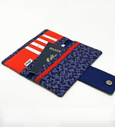 "Geometric Passport Wallet (by Minnebites) (3/3) - This handmade wallet is made with geometric patterned cobalt fabric with a bright, poppy red trim and interior. Room for a passport, bills, receipts, up to 8 credit cards (in 4 slots total). There is a snap closure and an interior zippered pocket. Measurements: Zipper opening is 7"", wallet is approximately 8"" x 4"" when closed."