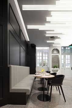 This bar area within a restaurant has black accent walls that match the black chairs, and dramatic lamella lighting on the ceiling. #RestaurantDesign #Lighting