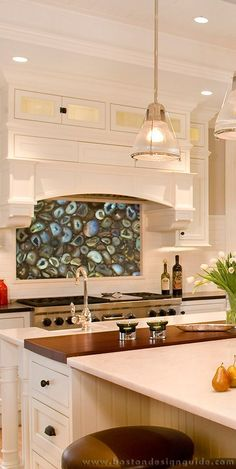 Kitchen cooktop with a marvelous custom backlit stone backsplash - Colin Smith Architecture