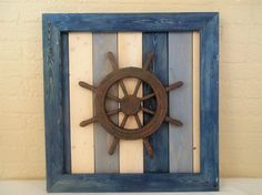 """Nautical Ships Wheel Framed Beach Cottage Wall Decor. Please note that each of our items is hand made and made to order. there is currently a 3-5 day shipping time on all items with the exception of cabinet knobs. Each item ordered from Twisted R Design is created in the order we receive the orders. 24""""x24"""" framed wall décor constructed of sanded pine wood finished with wood stain in shades of blue, white and gray and sealed with a clear coat. The colored stains that we use allow for a..."""
