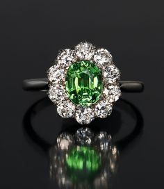 circa 1910  The ring is set with an exceptionally eye clean 1.42 ct Russian demantoid surrounded by ten old European cut diamonds (approximately 1.20 ct total diamond weight).  The great sparkle of this demantoid is due to its extraordinary clarity.