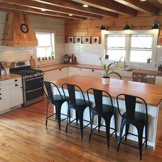 Farmhouse kitchen with wood beams, subway tile backsplash, butcher block countertops, wood covered range hood, IKEA farmhouse sink, shiplap, industrial style bar stools