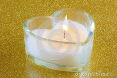 A closeup of a candle in a glass heart shaped holder