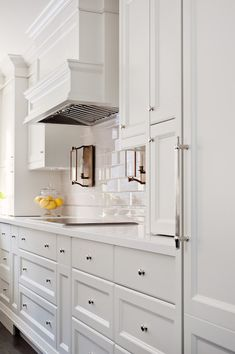 Exquisite kitchen features white shaker cabinets paired with white quartz countertops and subway tiled backsplash framing white paneled hood over copper lanterns above integrated cooktop situated next to small appliances cabinet and concealed refrigerator hidden behind paneled door.
