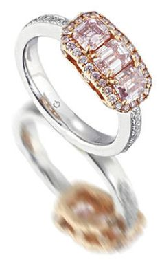 A coloured diamond and diamond three-stone ring. The step-cut fancy purplish pink diamond, weighing 0.61 carat, flanked by two similarly cut diamonds of pink hue within a similarly coloured brilliant-cut diamond surround, mounted in platinum and 18k pink gold, remaining coloured diamonds approximately 0.90 carat total, diamonds untested for natural colour, ring size 6¼. Via Bonhams.