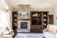 Floor-to-ceiling assymetrical stone fireplace flanked by wood built-in cabinets.