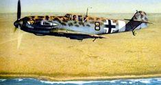 """Messerschmitt Bf 109 E-4/Trop """"Schwarze 8"""" of Oberfeldwebel Werner Schroer (8.Staffel / III.Gruppe / Jagdgeschwader 27) above the North African coast of Ain el Gazala/Libya, April 1941. The aircraft is wearing a short-lived leopard camo scheme."""