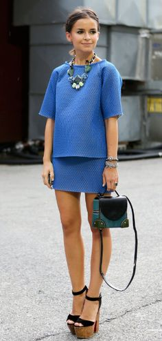 Matching blue boxy t-shirt and mini skirt + chunky black heels and cute green clutch