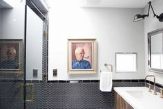 Black and white tiled walls, gold faucets, white sink, wooden sink base, glass shower, artwork