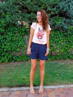 Tras la pista de Paula Echevarría » TROPICAL FLAVOR. White graphic t-shirt+dark blue shorts+silver embellished flat sandals+silver chain shoulder bag+sunglasses+silver watch. Summer Casual Outfit 2017