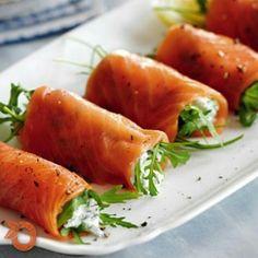 O salmão é um peixe rico em ômega 3, excelente para a saúde. Este aperitivo é de fácil preparo e fica uma delícia para servir aos seus convidados com um pãozinho ou simplesmente degustá-los puros! (y) Você vai precisar de 4 colheres de sopa de queijo cottage, 1 colher de chá de suco de limão, 2 colheres de sopa de endro bem picado, pimenta do reino moída, 16 tiras de salmão defumado e 75 g de rúcula. Junte o queijo cottage, o suco de limão e o endro picado em uma tigela. Tempere com pimenta