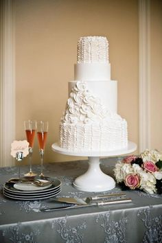 Four-tier buttercream cake with ruffles and roses