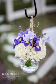 White and Purple Aisle Markers: Mason jars of white hydrangea, purple iris, lavender sweet peas and dried lavender hang from shepherd's hooks with natural twine to line the ceremony aisle by Andrea Layne Floral Design (www.andrealaynefloraldesign.com)