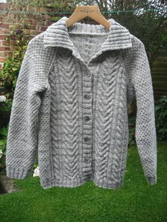 Cabled cardigan with round neck or collar.