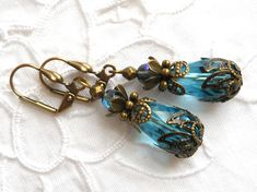 Filigree dangle earrings made of teal crystal faceted beads and brass and bronze beads and bead caps. The brass ox hook is nickelfree. The length of the earrings without the hook is approximately 3 cm. (1.2 inches) For more jewelry please visit our shop: http://www.minouc.etsy.com For