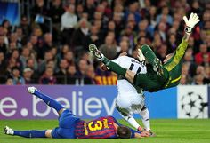 Victor Valdes races off his line to punch the ball away and flattens both Gerard Pique and Drogba in the process