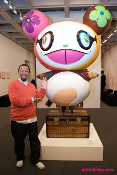 Takashi Murakami standing next to one of his Panda sculpture in fiberglass and polyester resin.