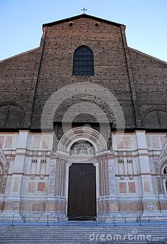 Photo made the Basilica of San Petronio in Bologna in Emilia Romagna (Italy). In the image taken by Maggiore square you see the central part of the facade remained incomplete in the upper part. In the picture you see the closed door of central entrance. Very beautiful the lower part of the wall covered with white marble.