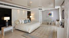 une chambre à coucher élégante et blanche avec un tapis en beige et bleu clair