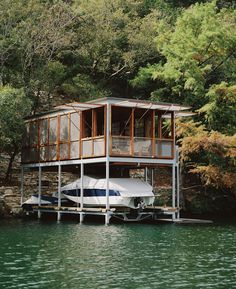 The Lake House pushes out from a steeply sloped bank and extends over Lake Austin in Texas. The lower portion of the rectangular building contains a sculling dock and boat storage, while the upper floor houses a furnished living area and grill. The structure serves as both a storage facility and a space for relaxation.