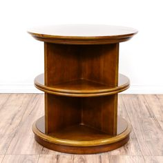 This round end table is featured in a solid wood with a glossy cherry finish. This side table is in good condition with 3 tier shelves, a round table top and curved trim. Unique table perfect for displaying books and knick knacks! #contemporary #tables #endtable #sandiegovintage #vintagefurniture