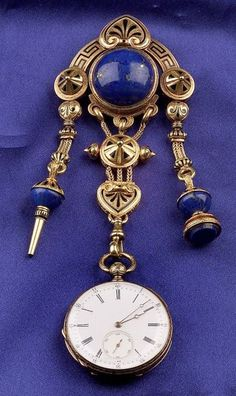 Antique 18kt Gold, Lapis and Enamel Pocket Watch and Chatelaine, Czapek et Cie, the black tracery enamel form with key and seal highlighted by lapis boss suspending an openface watch with white enamel dial with subsidiary seconds dial, lapis panel case enclosing nickel keywind movement, 30 mm, lg. 5 in., French guarantee stamps, (chatelaine hook converted to brooch, crack to lapis).   Estimate $1,200-1,500  Sold for $1,900