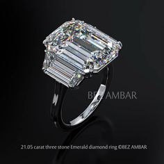This 21.05 carat emerald shape diamond and two large trapezoid diamonds were masterfully cut to elegantly accentuate each other create this captivating three stone engagement ring.