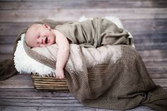 Cutie pie baby boy sleeping in wooden basket and smiling. Photographed at Julie Saad Photography in Williamsburg, Brooklyn.