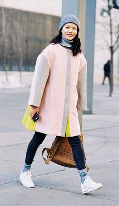 A turtleneck sweater is paired with a pastel coat, skinny jeans, Nike sneakers, and a beanie