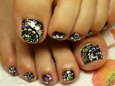 Toenails pedicure with black polish and silver glitter dots
