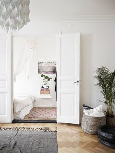 Love the colors! - Gray rug, Basket for storage, pouf, white bedroom & linens, wood floor --- Tiny Stylish Apartment In Sweden