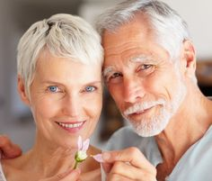 Closeup portrait of a mature couple playing with a flower