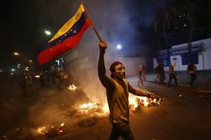 Photos From the Anti-Government Protests in Venezuela : An opposition demonstrators holds a Venezuelan flag in front of a burning barricade during a protest against President Nicolas Maduro's gove...
