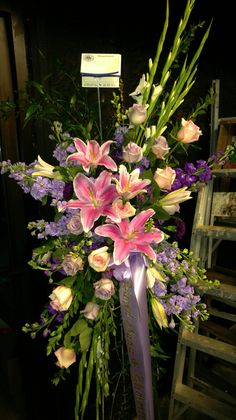 Funeral spray of many colors to remember a loved one at the service. americasflorist.com