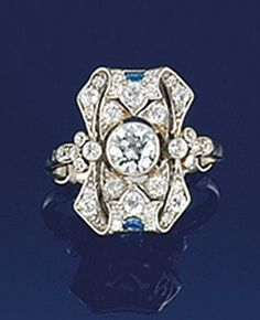 An early 20th century diamond and sapphire ring  The central brilliant-cut diamond collet within an old-cut diamond pierced shaped panel with scroll terminals and lunette shaped sapphire accents, to diamond shoulders and plain hoop, circa 1925