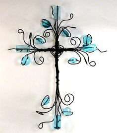 This cross features swirls of black wire with acrylic beads of turquoise intertwined within the wire. It measures about 12 inches tall,8
