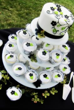 """This is a 6"""" cake with black and green fondant flowers, vanilla cupcakes with reversible cupcakes wrappers"""